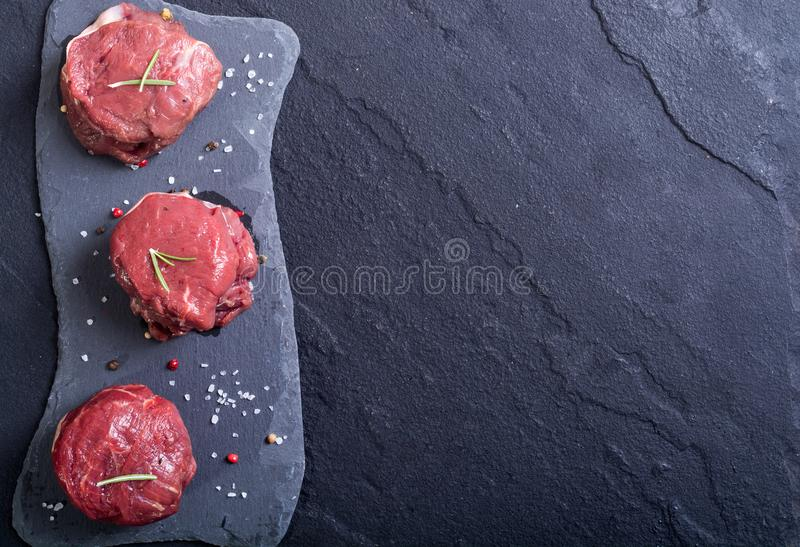 Raw fillet mignon. With pepper , salt on stone background royalty free stock photography