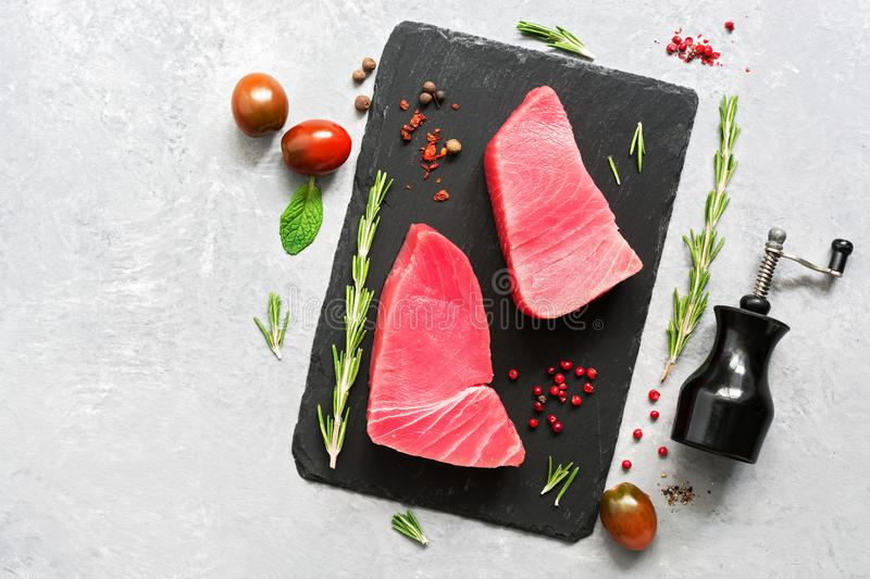Raw fillet steak tuna with herbs and spices on gray background. Top view, flat lay.  royalty free stock photos
