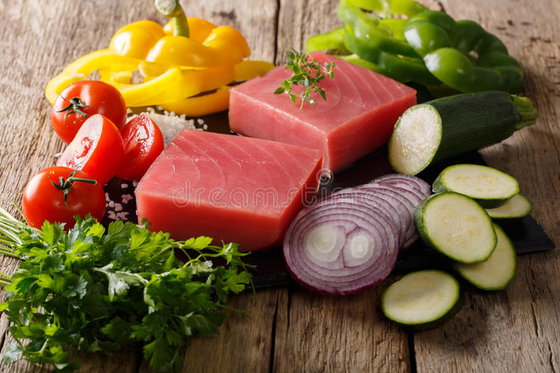 Raw fillet of tuna with pepper, onions, tomatoes, zucchini and g. Reens close-up on the table. horizontal royalty free stock images