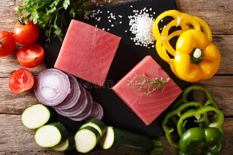 Raw fillet of tuna with pepper, onions, tomatoes, zucchini and g. Reens close-up on the table. Top view from above horizontal stock image