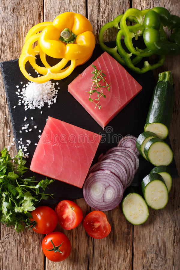 Raw fillet of tuna with pepper, onions, tomatoes, zucchini and g. Reens close-up on the table. Top view from above vertical royalty free stock images
