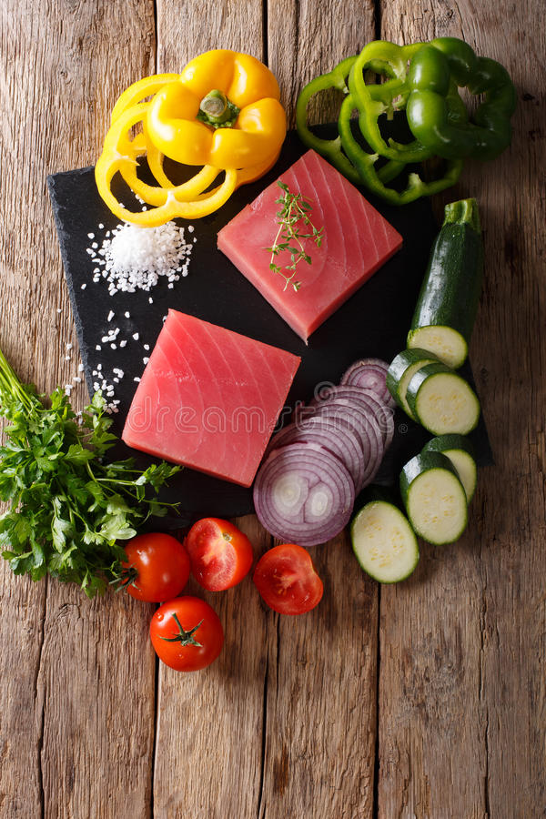 Raw fillet of tuna surrounded by fresh vegetables and spices close-up. Vertical top view. Raw fillet of tuna surrounded by fresh vegetables and spices close-up stock image