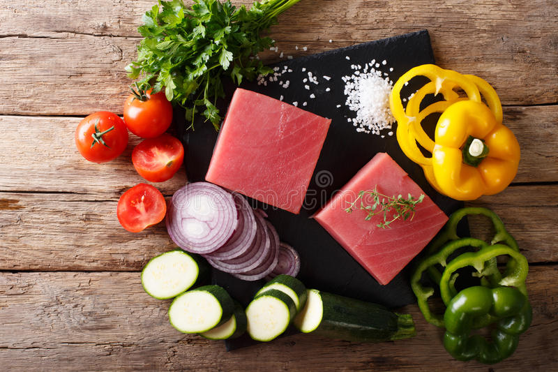 Raw fillet of tuna surrounded by fresh vegetables and spices close-up. Horizontal top view. Raw fillet of tuna surrounded by fresh vegetables and spices close-up royalty free stock photography