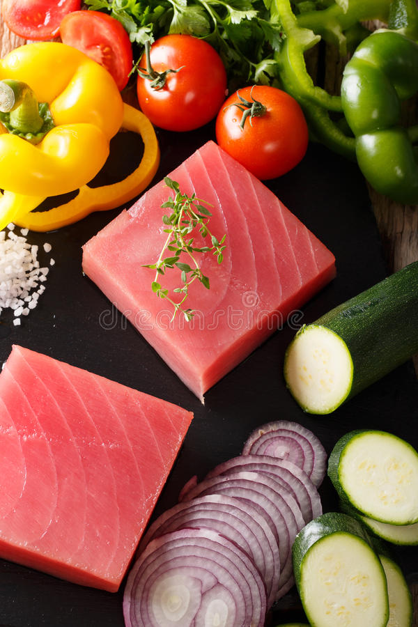 Raw fillet of tuna surrounded by fresh vegetables and spices close-up. vertical. Raw fillet of tuna surrounded by fresh vegetables and spices close-up on a royalty free stock photography