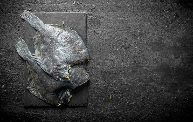 Raw fish on a black stone Board. On black rustic background royalty free stock photo