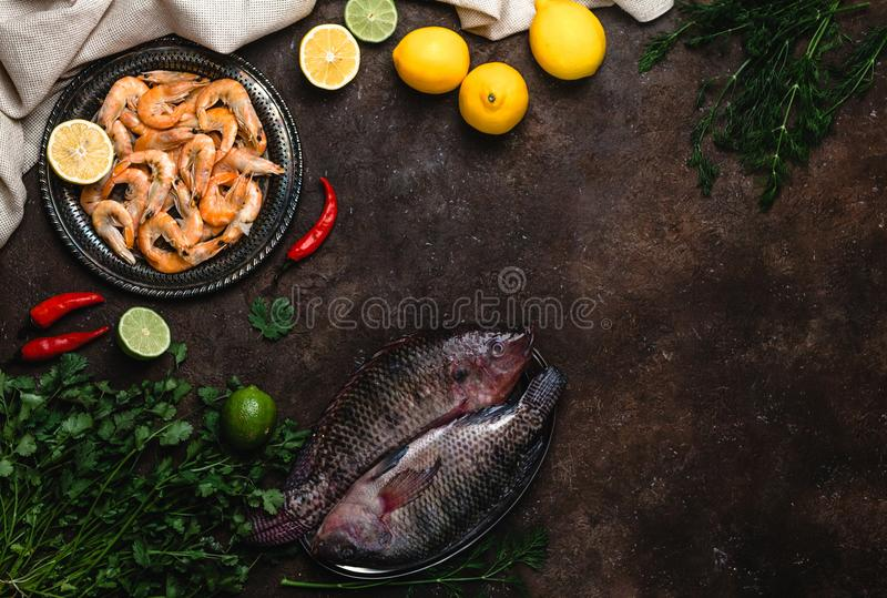 Download Raw Fish, Chili Peppers, Shrimp, Herbs With Lemons And Tablecloth  Stock Photo