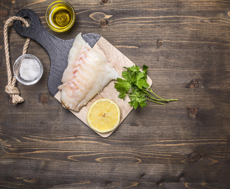 Raw fish fillet on a cutting board with lemon, herbs, butter and salt border ,place for text wooden rustic background top view stock images
