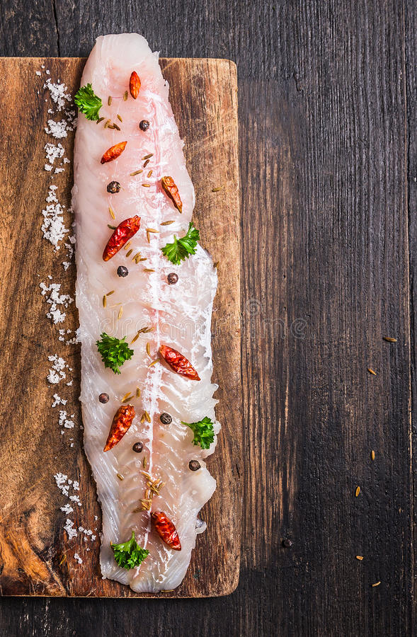 Raw Fish fillet with herbs and spices on dark cutting board stock photography