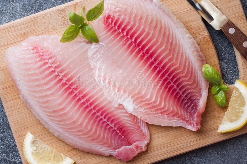 Raw fish fillet of tilapia on a cutting Board with lemon and spices. Dark table stock photos