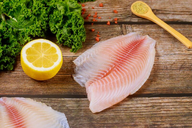 Raw fish fillet of tilapia on table with lemon and spices royalty free stock images