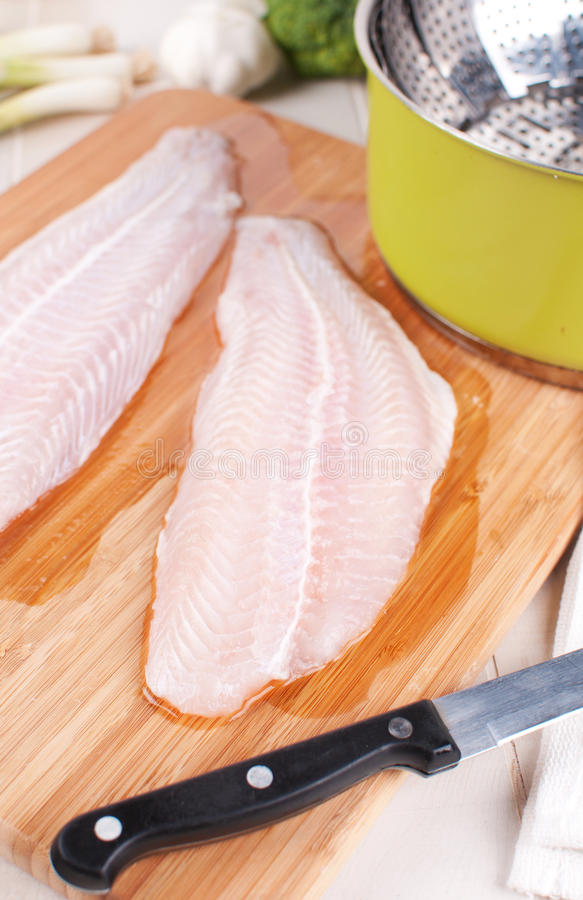 Raw fish fillets on cutting board stock image