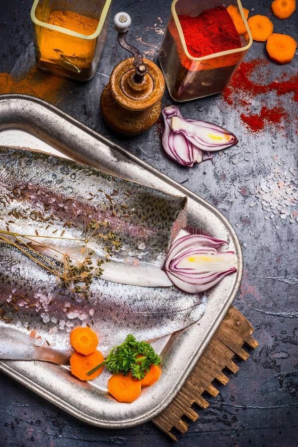 Raw fish fillets with spices, cooking preparation on dark kitchen table royalty free stock image