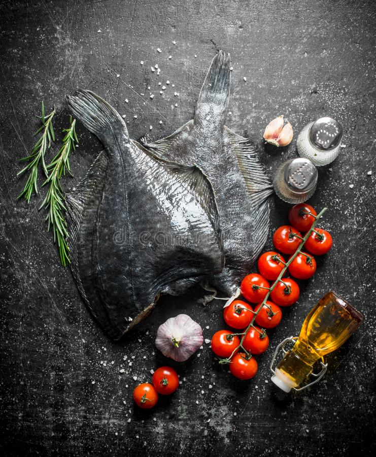 Raw fish flounder with cherry tomatoes, spices and garlic. On dark rustic background royalty free stock images
