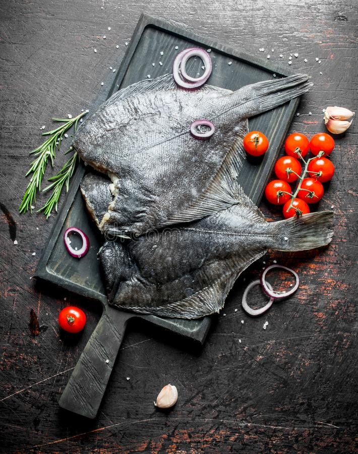 Raw fish flounder on a cutting Board with cherry tomatoes and sliced onions. On dark rustic background stock photography