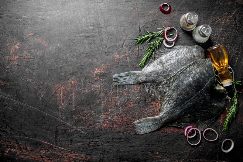 Raw fish flounder with rosemary, spices and onion rings. On dark rustic background stock photography