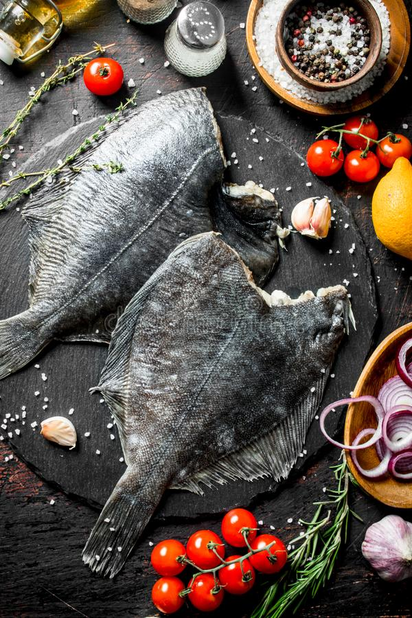 Raw fish flounder with spices, tomatoes, chopped onion and garlic. On dark rustic background stock images