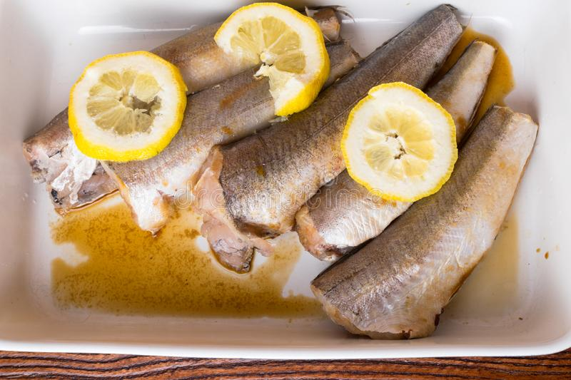 Raw fish hake with lemon slices, spices, olive oil on white pan stock image