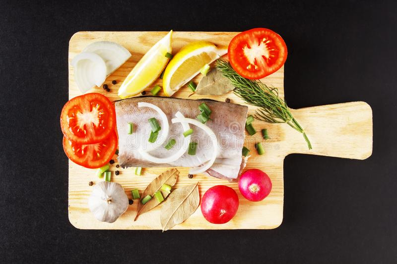 Raw fish meat, organic radish, lemon, onion and spice top view with closeup on cutting board. Fresh natural, organic, healthy and royalty free stock images