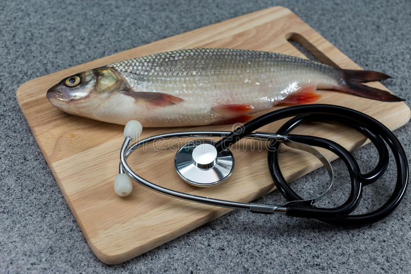 Raw fish, not cooked. White fish on a cutting Board and a knife. royalty free stock photos