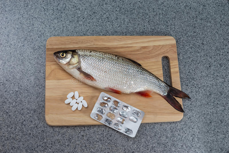 Raw fish, not cooked. White fish on a cutting Board and pills. royalty free stock images