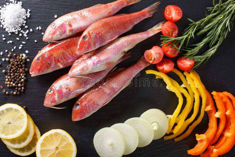 Raw fish red mullet with ingredients close-up on the table. horizontal top view stock photo