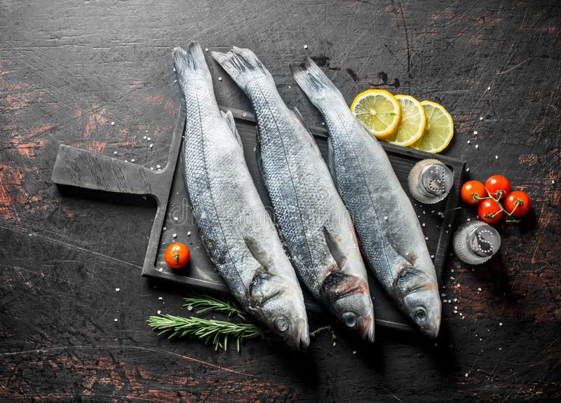 Raw fish sea bass with lemon, rosemary and spices. On dark rustic background royalty free stock image