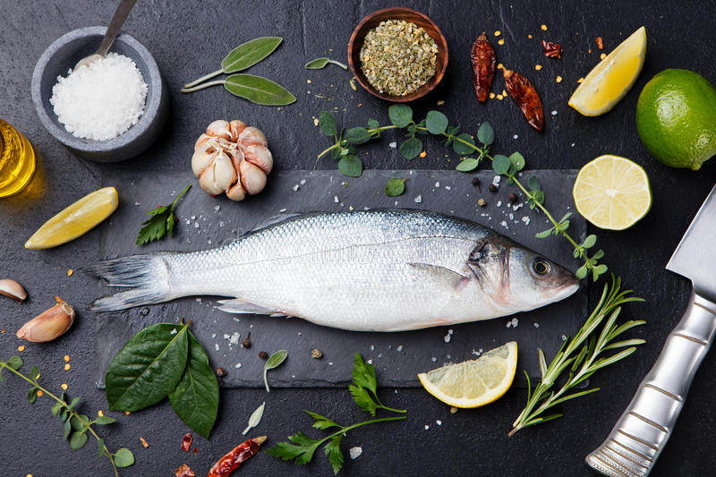 Raw fish, sea bass on slate black board Top view. Raw fish, sea bass on slate black board. Ingredients for cooking, grill, roasting. Top view Copy space stock image
