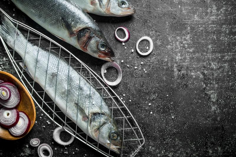 Raw fish seabass on the grill with chopped onions. On dark rustic background royalty free stock photo
