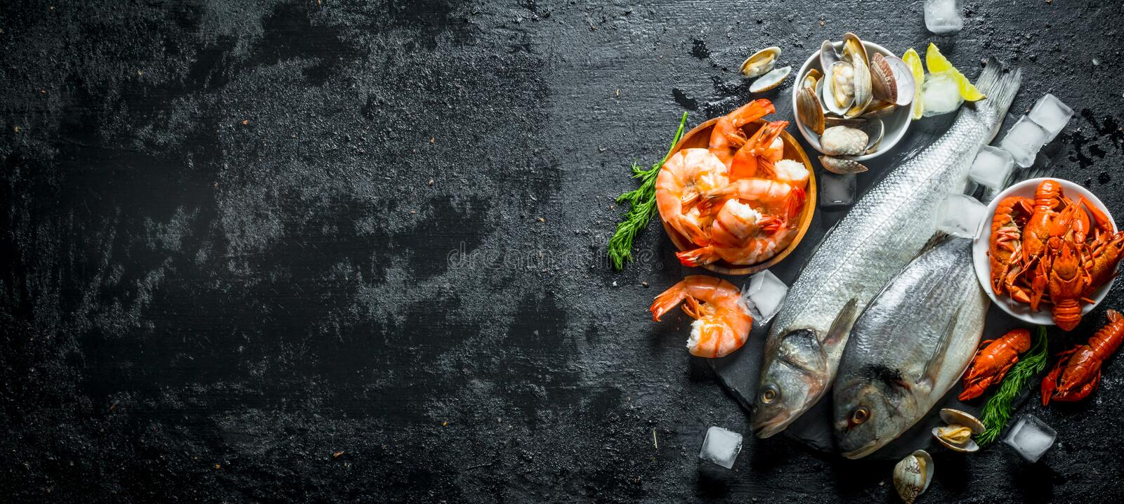 Raw fish and seafood on a stone Board with ice cubes and lime slices stock photo
