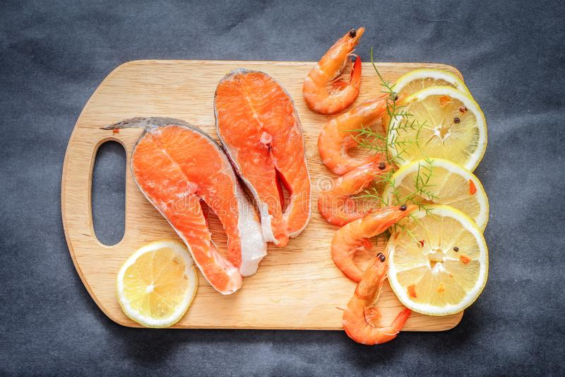 Closeup of chopped salmon with lemon slice on wooden board on gray crafty table top royalty free stock photo