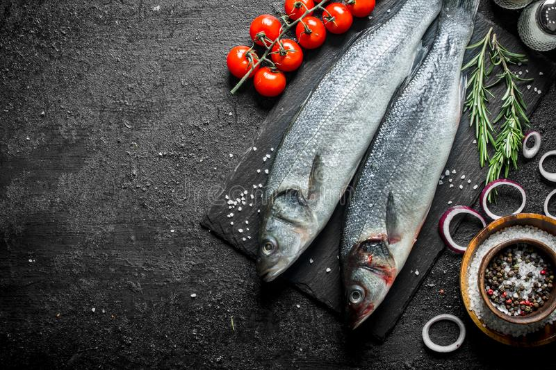 Raw fish with spices, cherry tomatoes and chopped onions. On black rustic background royalty free stock image