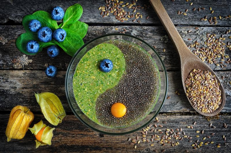 Raw flaxseed porridge with chia. Healthy breakfast. Raw flaxseed porridge with chia seeds, spinach, physalis and fresh blueberries on wooden table, top view stock images