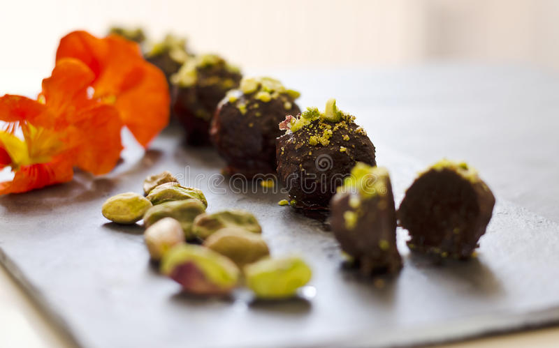 Raw food pralines. Raw food chocolate pralines on a dark plate with decoration stock photos