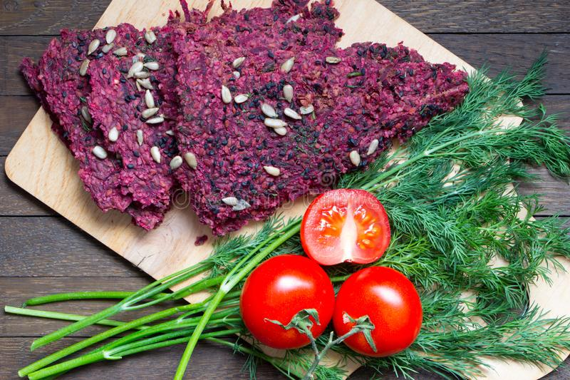 Raw foods. Dry vegan bread loaves from beet and walnut on kitchen board on wooden table. Dehydrated vegan dry bread loaves cooked by low baking from beet, walnut royalty free stock photos