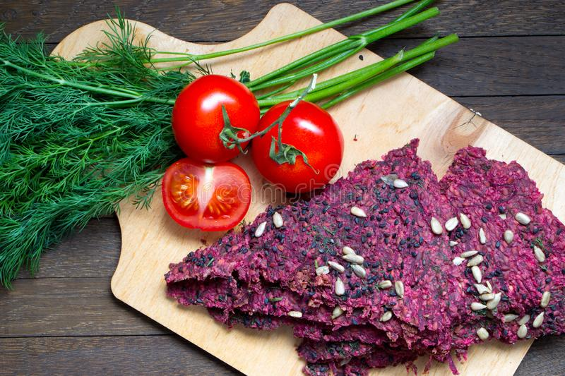 Raw foods. Vegan dry bread loaves, tomatoes and dill on kitchen board on wooden table. Vegan dry bread loaves cooked by low baking in dehydrator from beet stock images
