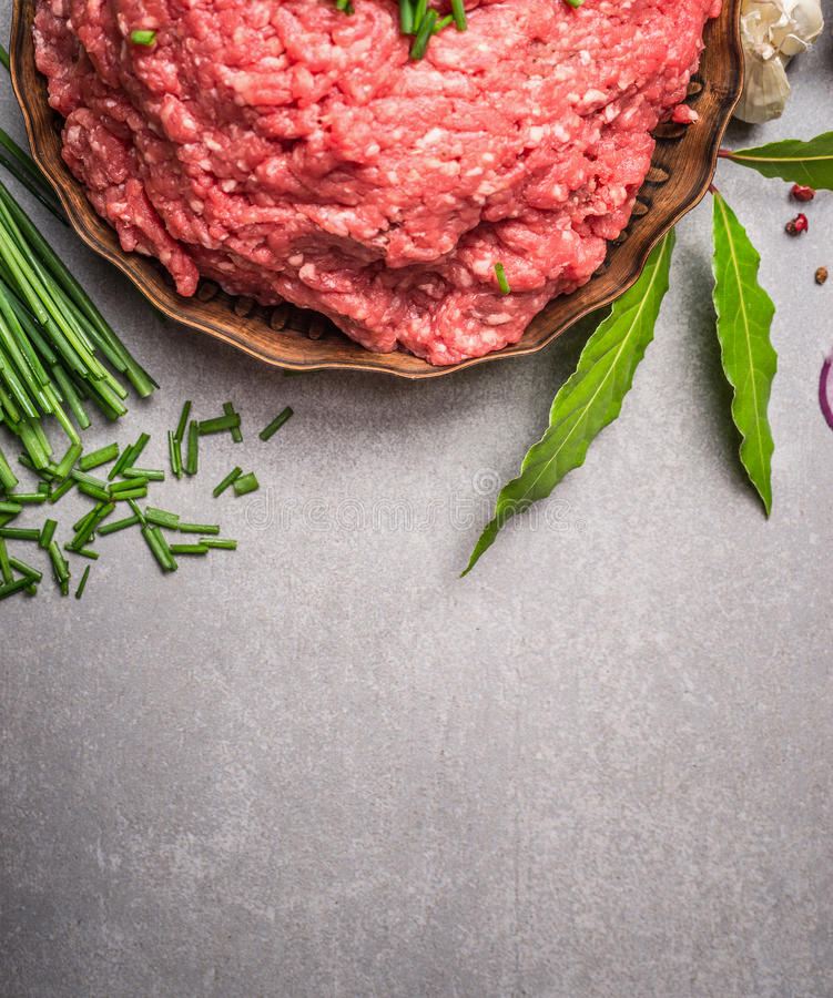 Raw force meat and fresh green seasoning ingredients for tasty cooking on stone background. Top view, border royalty free stock images