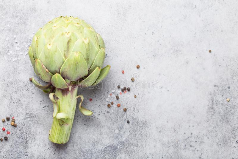 Raw fresh artichoke. Close-up of raw fresh artichoke with seasonings ready to cook, great as vegetarian food or ingredient for healthy salads and diets, grey royalty free stock photography