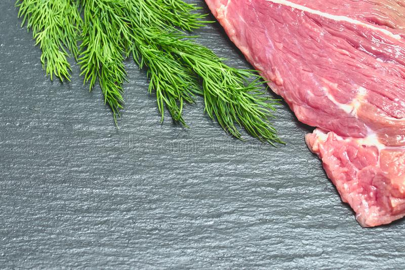 Raw fresh beef meat on a black background with a sprig of dill stock images