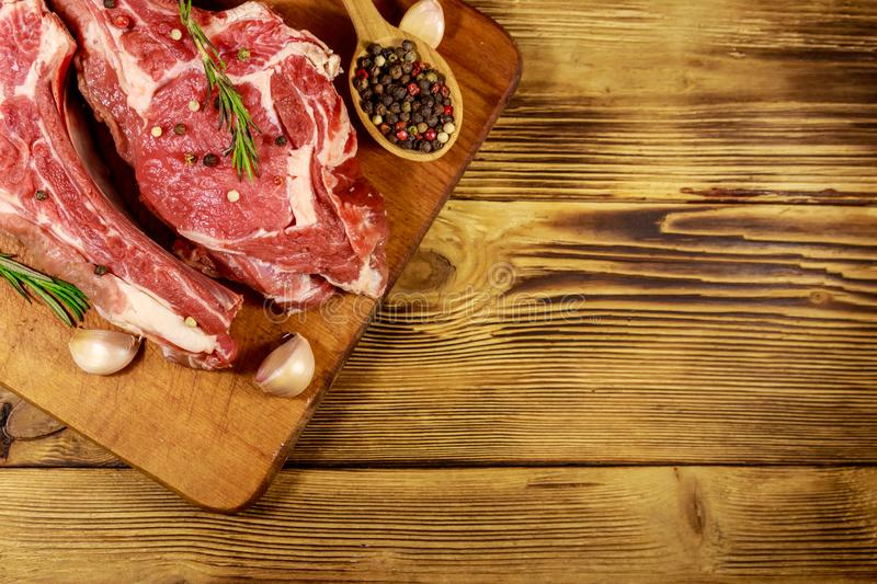 Raw fresh beef rib eye steak on bone with spices, garlic and rosemary on wooden table. Top view royalty free stock photo