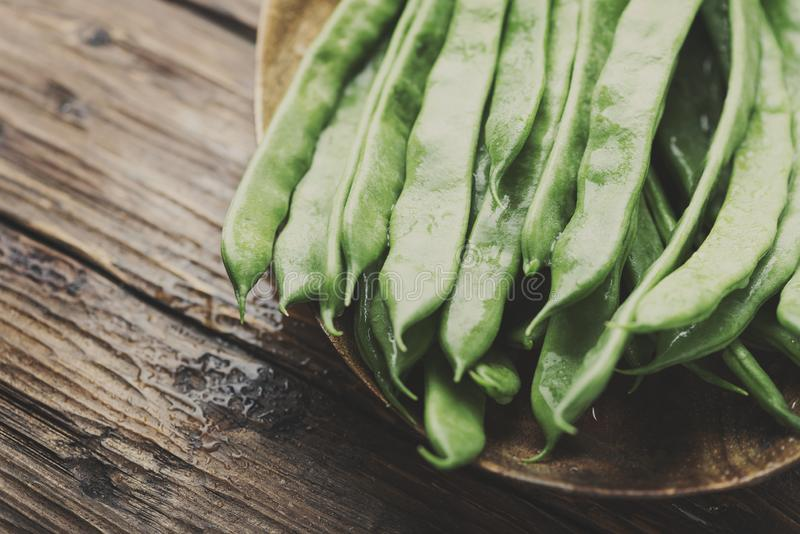Raw fresh green beans. On the wooden table, selective focus and toned image royalty free stock photos