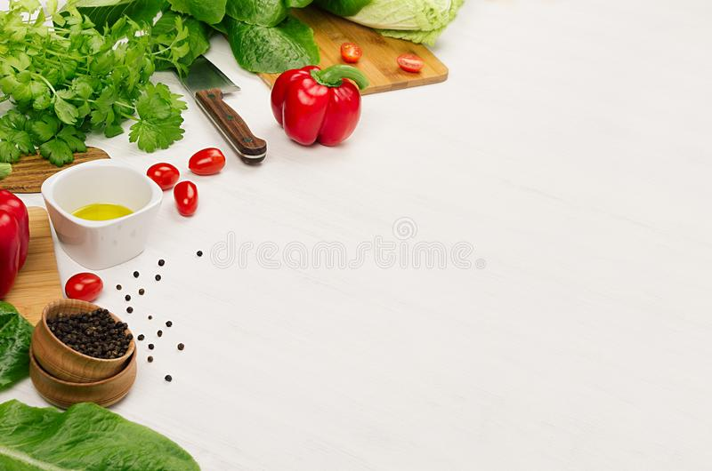 Raw fresh green vegetables, greens, red cherry tomatoes and kitchenware on soft white wood board, border. Spring vitamin dieting food royalty free stock photography