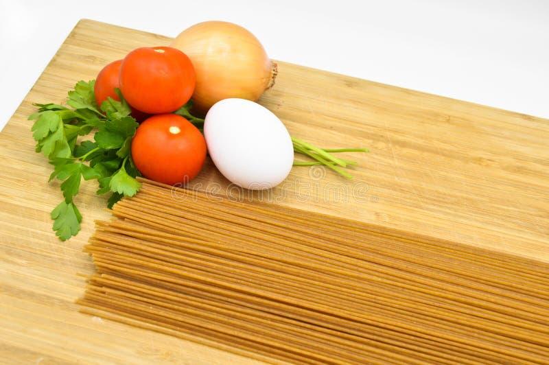 Raw and fresh macaroni, tomatoes, egg and onion. Raw and fresh macaroni, tomatoes and egg  on cutting board stock image
