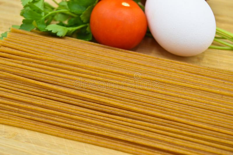 Raw and fresh macaroni, tomatoes, egg and onion. Raw and fresh macaroni, tomatoes and egg  on cutting board royalty free stock photography