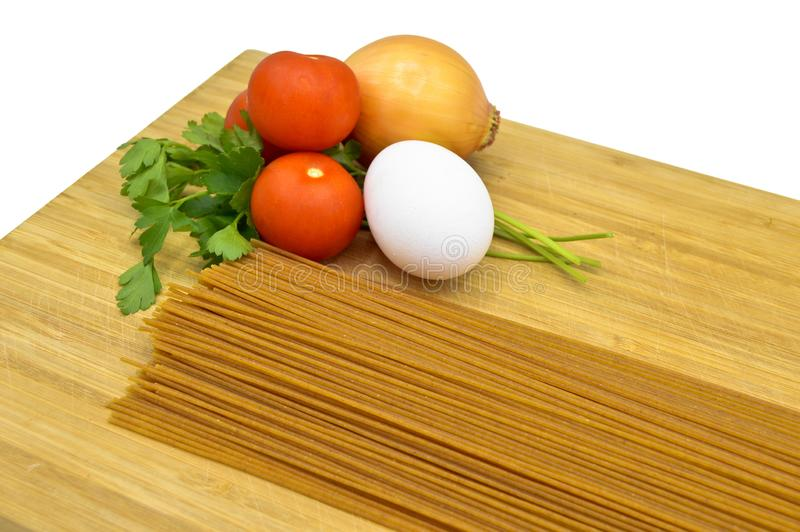 Raw and fresh macaroni, tomatoes, egg and onion. Raw and fresh macaroni, tomatoes and egg  on cutting board royalty free stock photos