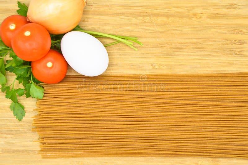 Raw and fresh macaroni, tomatoes, egg and onion. Raw and fresh macaroni, tomatoes and egg isolated on cutting board stock image