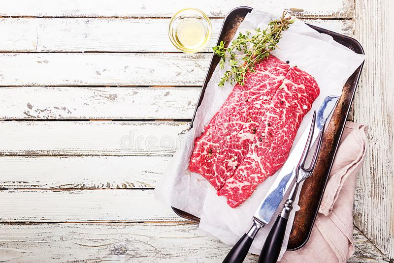 Raw fresh marbled meat. Beef Steak and seasonings on paper over white wooden background royalty free stock images