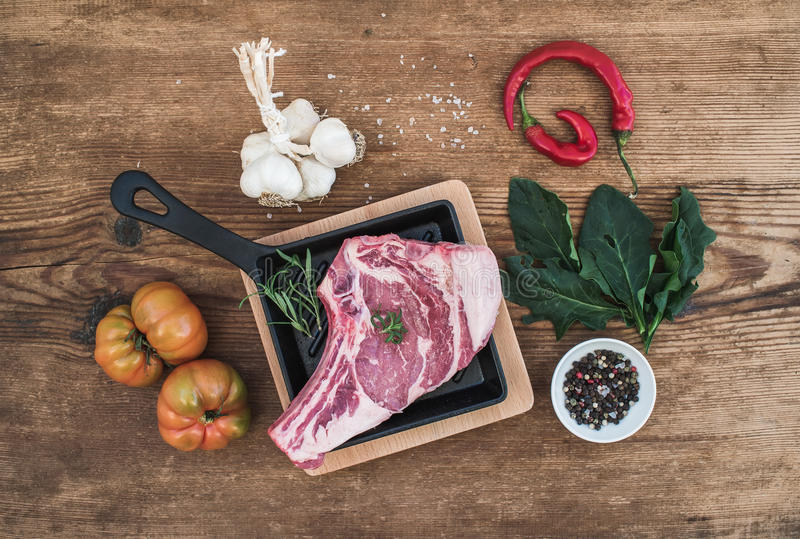 Raw fresh meat ribeye steak with pepper, salt, chili, garlic, spinach, heirloom tomatoes and rosemary in cooking pan royalty free stock photo