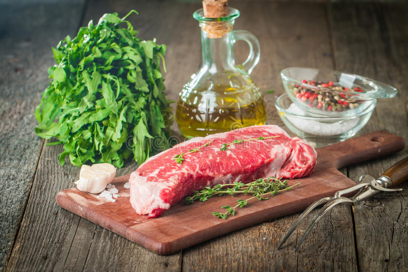 Raw fresh meat ribeye steak. Pepper, salt and thyme on cutting board with meat fork on background royalty free stock photos