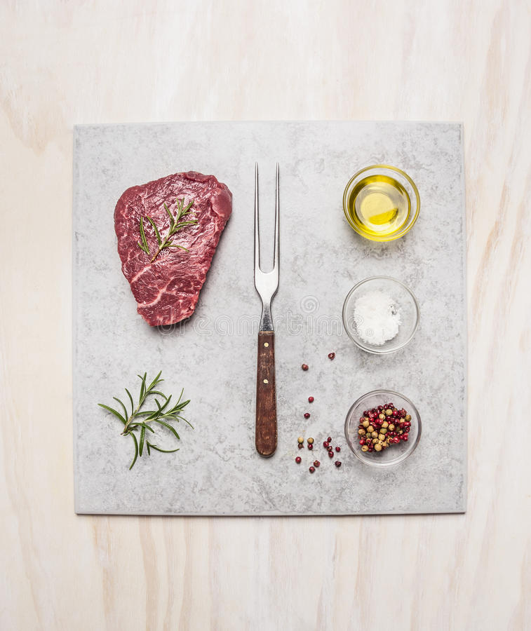 Raw fresh meat Steak with spice ingredients on light marble plate over wooden background, top view stock images