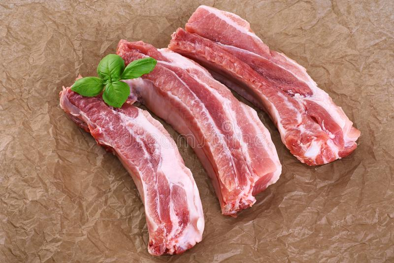 Raw fresh pork ribs and basil on the background of craft paper. royalty free stock images